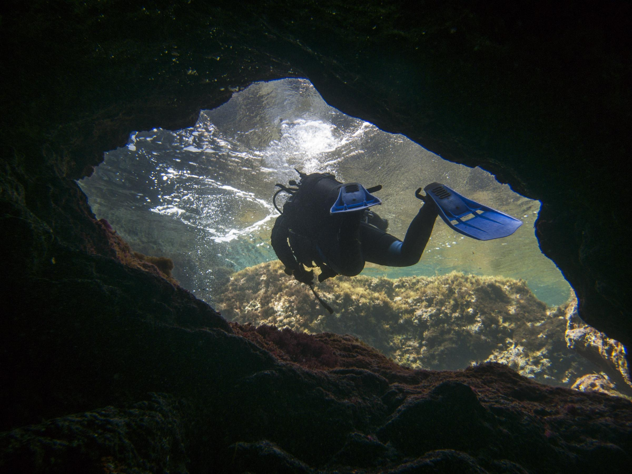 Diver exiting the cave in Ghar Lapsi